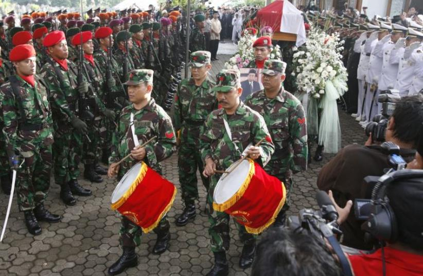 Soldiers carry the coffin of former Indonesian President Abdurrahman Wahid (also known as Gus Dur) as they leave the residence in Jakarta, December 31, 2009 (photo credit: REUTERS)