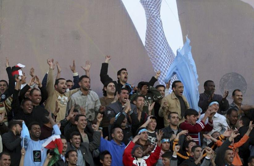 Fans cheer Jordan's Al-Faysali team during a soccer match against Morocco's Al Raja during their Arab Champions League in Amman March 12, 2008 (photo credit: REUTERS)