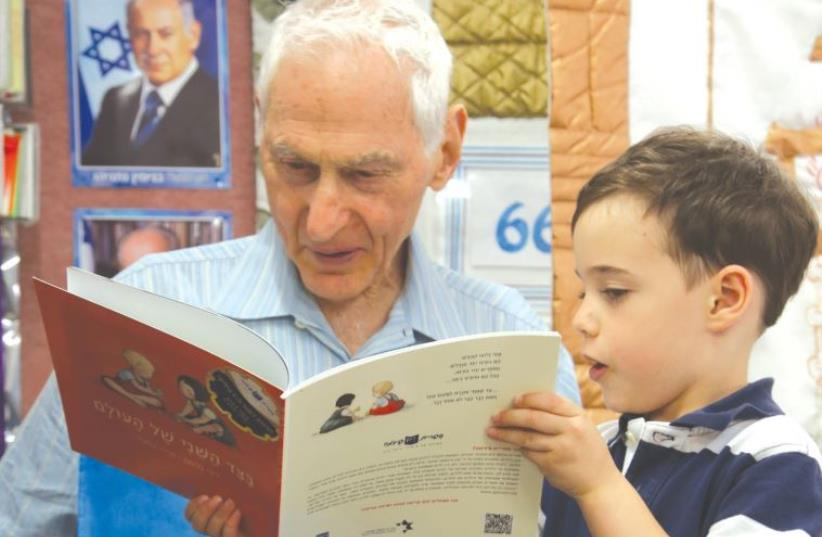 HAROLD GRINSPOON reads to a child one of the 10 million children's books his foundation has given away (photo credit: Courtesy)