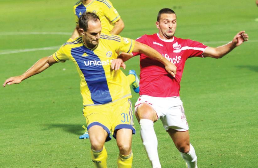 Maccabi Tel Aviv defender Carlos Garcia (left) and Hapoel Beersheba striker Ben Sahar battle for the ball during last night's 0-0 draw at Bloomfield Stadium. (photo credit: ADI AVISHAI)