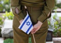 An Israeli soldier holds a flag next to the grave of a fallen soldier