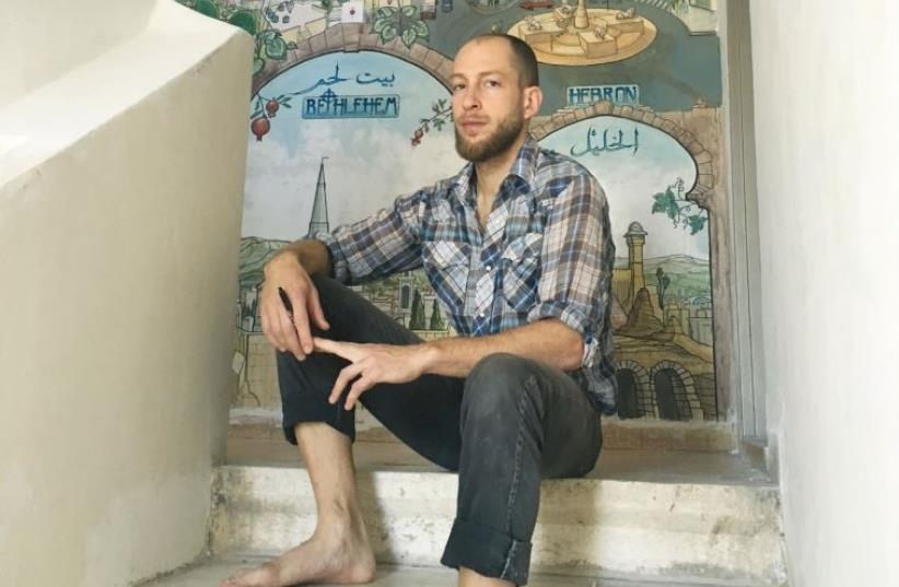Hillel Efflal sits in front of his mural at the Hostel in Ramallah (photo credit: MAX SCHINDLER)