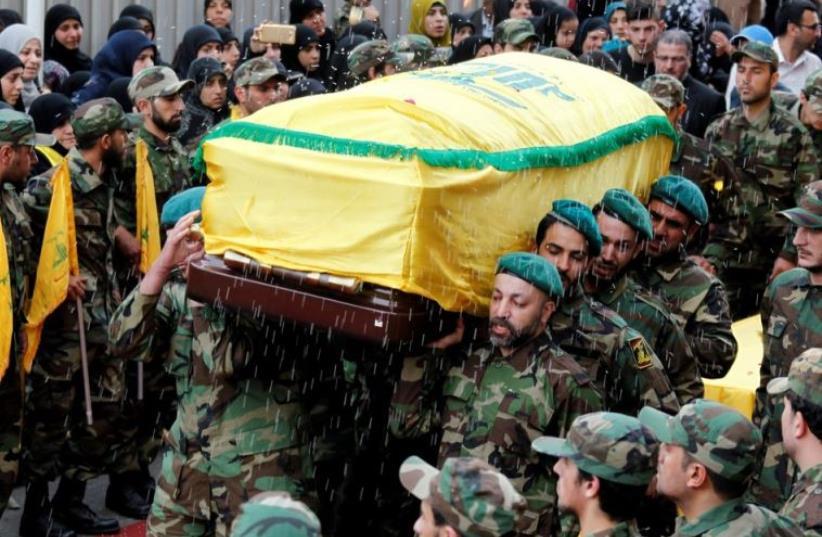 Rice is thrown as Hezbollah members carry the coffin of top Hezbollah commander Mustafa Badreddine (photo credit: REUTERS)