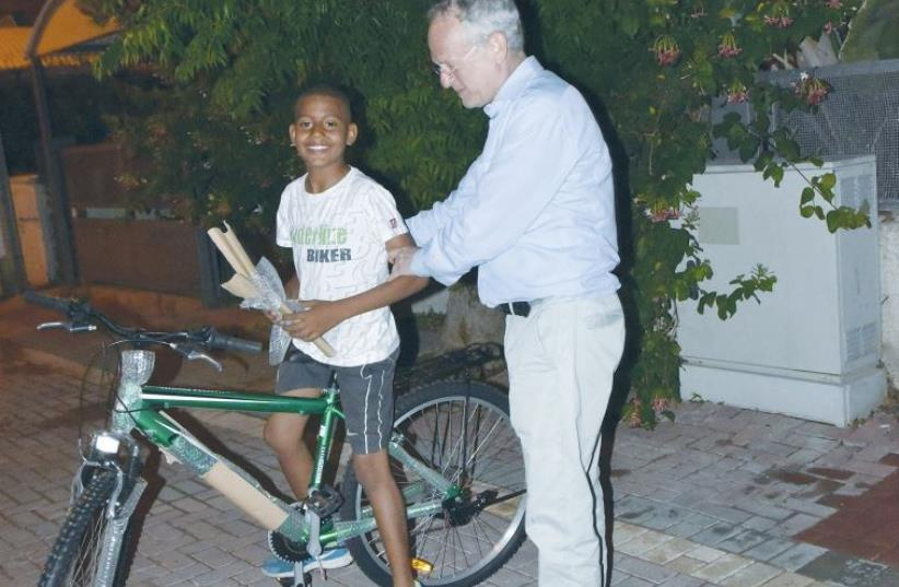 ONEFAMILY founder and chairman Marc Belzberg presents a bicycle yesterday to a son of slain taxi driver Amin Shaaban. (photo credit: SARAH LEVIN)