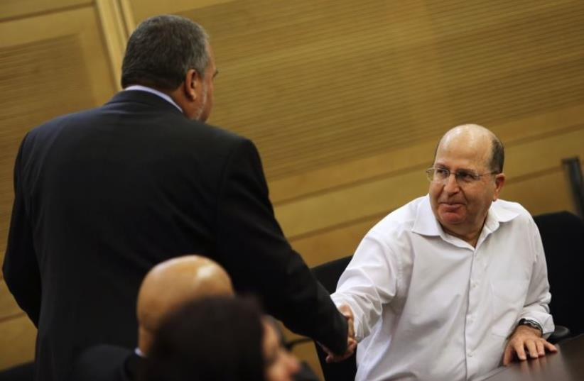 Moshe Ya'alon (R) shakes hands with Avigdor Liberman at the Knesset in Jerusalem (photo credit: REUTERS)