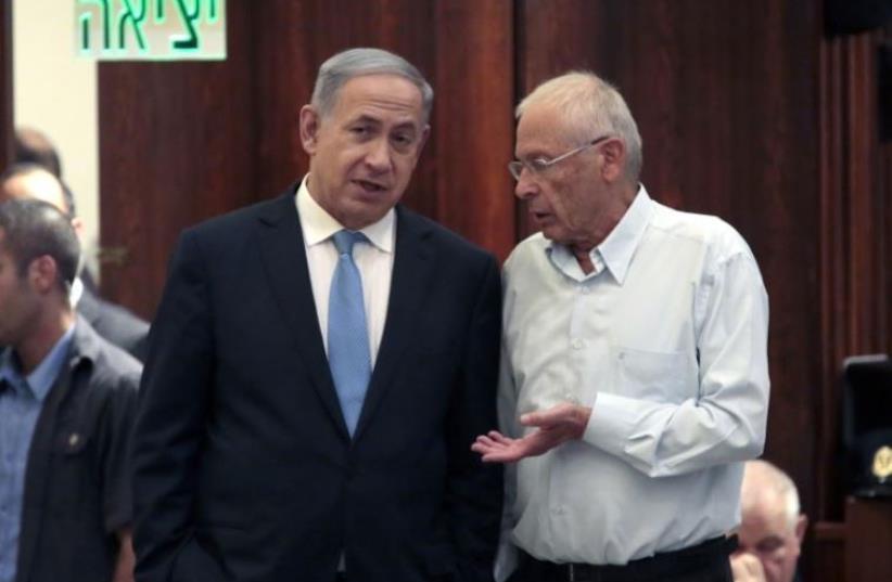 Prime Minister Benjamin Netanyahu (L) and Bennie Begin confer in the Knesset (photo credit: AFP PHOTO)