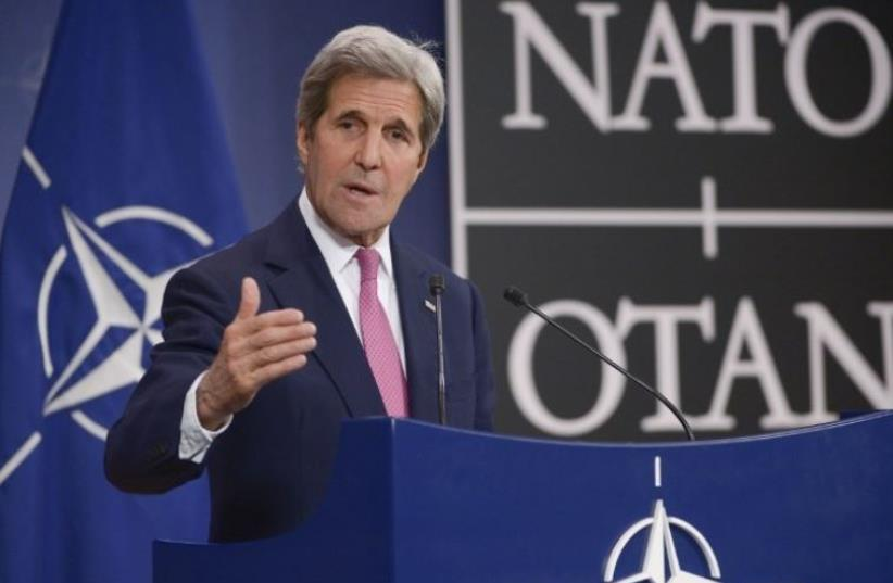 US Secretary of State John Kerry speaks to the press at NATO headquarters in Brussels (photo credit: AFP PHOTO)