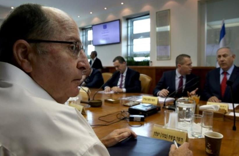 Defense Minister Moshe Yaalon (L) takes part in the weekly cabinet meeting chaired by Prime Minister Benjamin Netanyahu (R) (photo credit: AFP PHOTO)