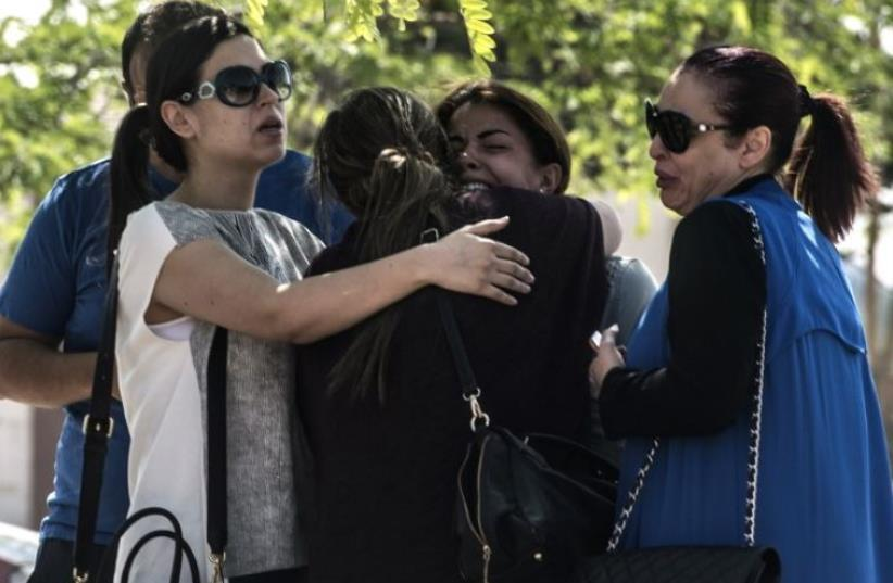Families of passengers who were flying in an EgyptAir plane that vanished from radar en route from Paris to Cairo react as they wait outside a services hall at Cairo airport (photo credit: AFP PHOTO)