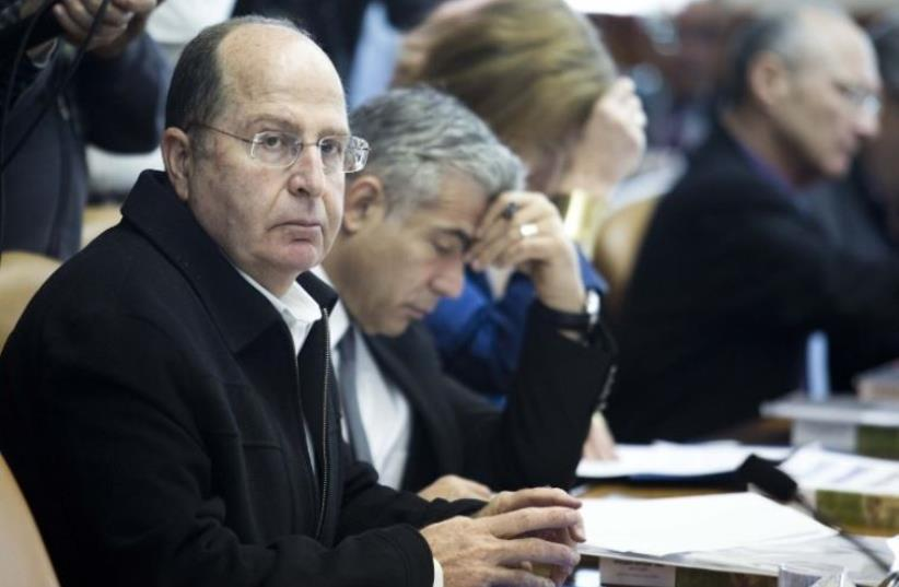 Defense Minister Moshe Ya'alon (L) looks on during a cabinet meeting in Jerusalem (photo credit: AFP PHOTO)