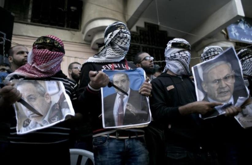 Palestinians hold knives in front of posters of Prime Minister Benjamin Netanyahu (R), Avigdor Liberman (C) and former premier Ehud Barak (photo credit: AFP PHOTO)