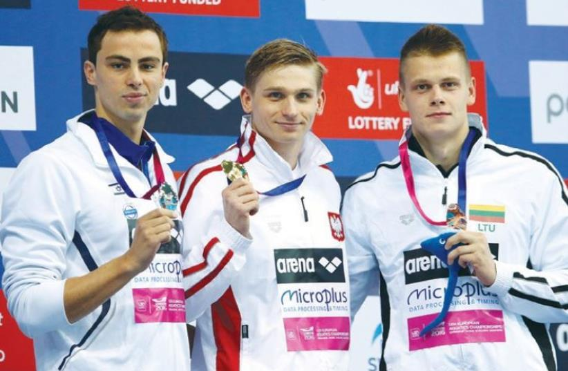 Israel swimmer Yakov Toumarkin (left) claimed the blue-and-white delegation's second medal at the European Championships in London yesterday, ending the 200-meter backstroke final in second place behind Poland's Radoslaw Kawecki (center) and ahead of bronze medalist Danas Rapsys of Lithuania. (photo credit: REUTERS)
