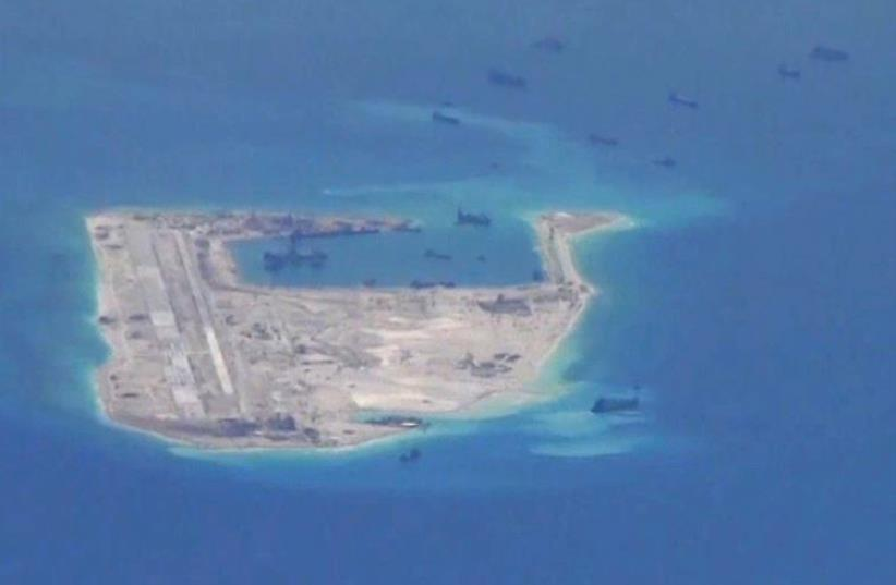Chinese dredging vessels are purportedly seen in the waters around Fiery Cross Reef in the disputed Spratly Islands in the South China Sea in this still image from video taken by a P-8A Poseidon surveillance aircraft provided by the United States Navy May 21, 2015.  (photo credit: US NAVY/HANDOUT VIA REUTERS)