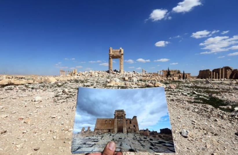 A general view taken on March 31, 2016 shows a photographer holding his picture of the Temple of Bel taken on March 14, 2014 in front of the remains of the historic temple after it was destroyed by Islamic State (photo credit: AFP PHOTO)