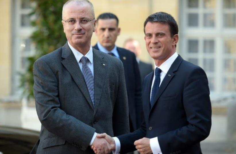 French Prime minister Manuel Valls (R) shakes hands with Palestinian prime minister Rami Hamdallah (photo credit: AFP PHOTO)