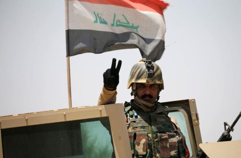 An Iraq soldier gestures near Falluja, Iraq (photo credit: REUTERS)