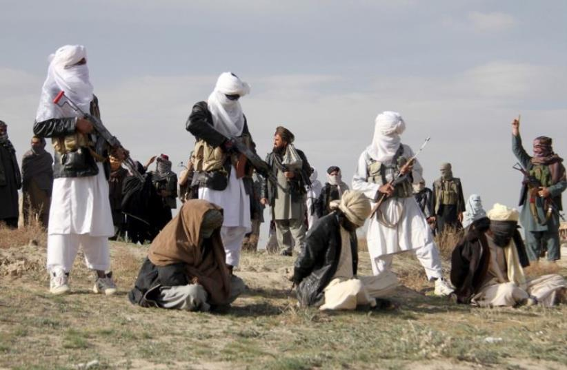 Taliban insurgents stand over three men, accused of murdering a couple during a robbery, before shooting them during their execution in Ghazni Province, Afghanistan (photo credit: REUTERS)
