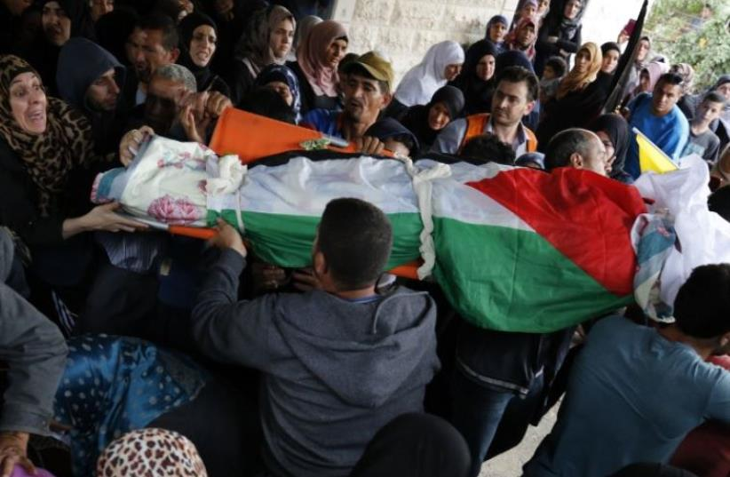 Palestinian mourners carry the bodies of Maram Abu Ismail, 23, and her brother Ibrahim Taha, 16, who were shot dead by Israeli police last month at the Qalandiya checkpoint (photo credit: AFP PHOTO)