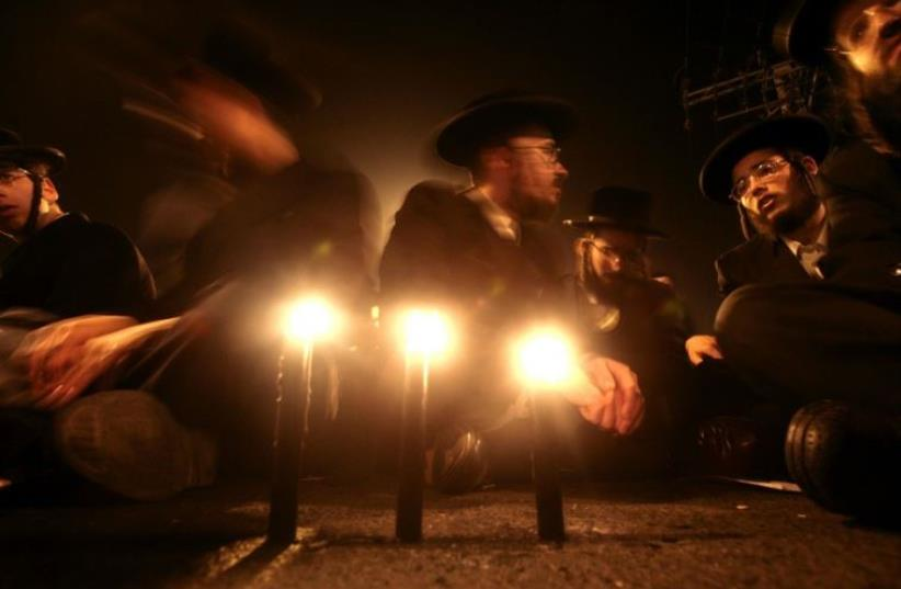 Ultra-Orthodox Jews light candles in Jerusalem (photo credit: REUTERS)