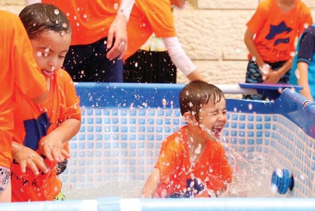 Splashing around at Ezrat Achim's Special Summer Camp 2015 (photo credit: DAVID ABITBOL)