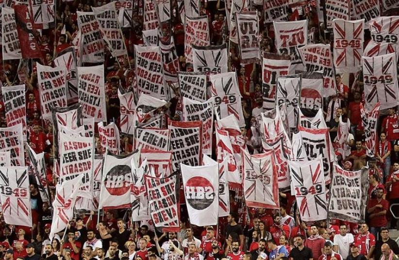 Enthusiastic Hapoel Beersheba fans hoist banners (photo credit: DANNY MAROM)