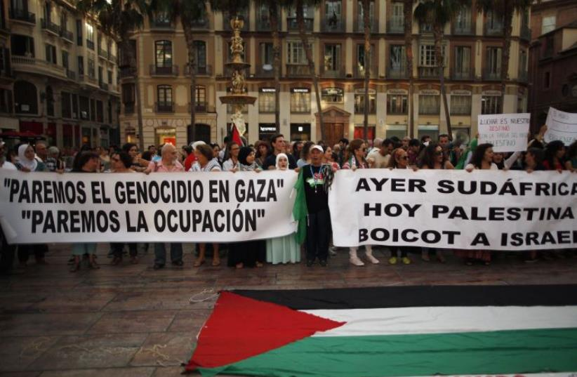 People hold banners during a protest against Israel's military action in Gaza, at La Constitucion square in Malaga, Spain [File] (photo credit: REUTERS)