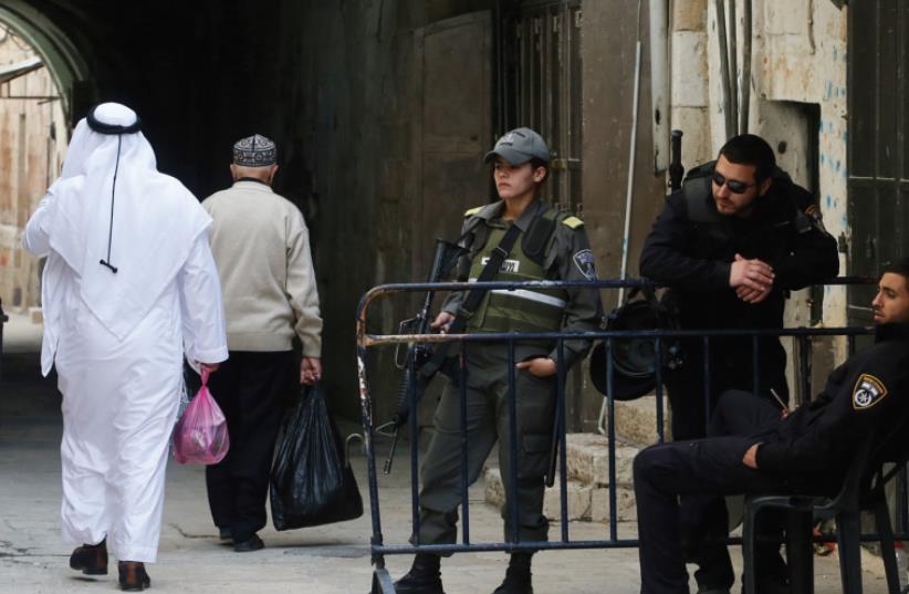 A SPLIT CITY: Two Arab men walk past police officers in the Old City of Jerusalem (photo credit: MARC ISRAEL SELLEM)