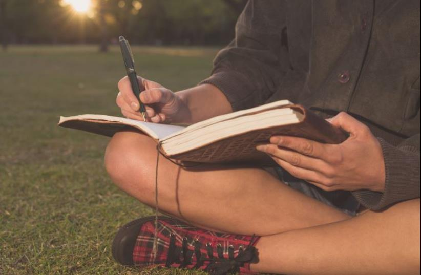 A young woman is sitting on the grass in a park at sunset and is writing in a notebook (illustrative) (photo credit: INGIMAGE)