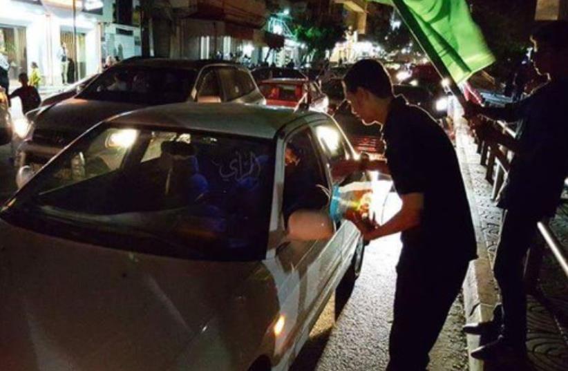 Youth in Tulkarm distributing candies (photo credit: ARAB MEDIA)