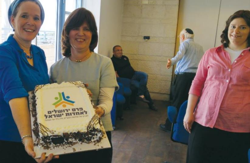 Rachelle Sprecher Fraenkel (left) and Tzila Schneider hold a cake celebrating the Jewish Unity Prize (photo credit: Courtesy)