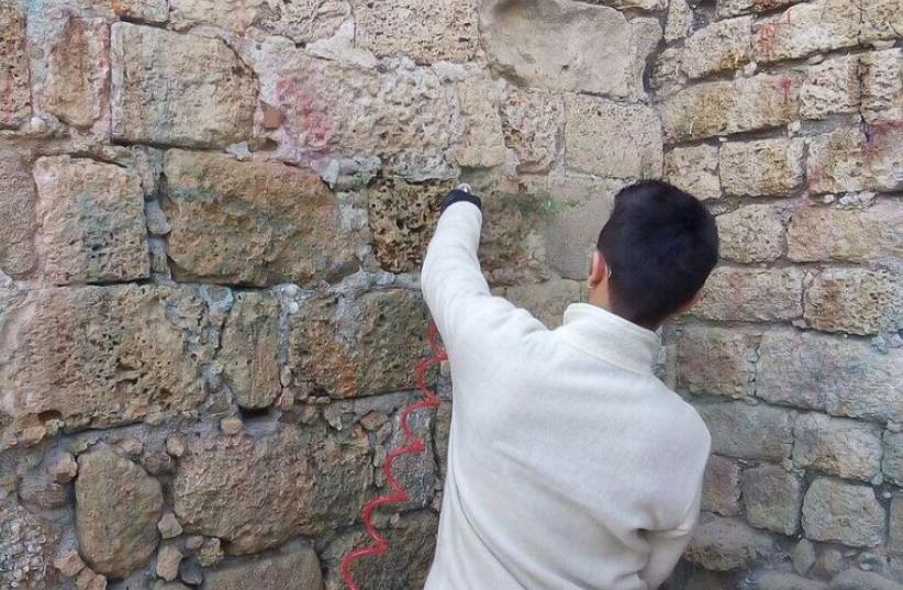 One of the teenagers responsible for dousing the wall in paint works with IAA archeologists to restore it. (photo credit: ARIEL INBAR/IAA)