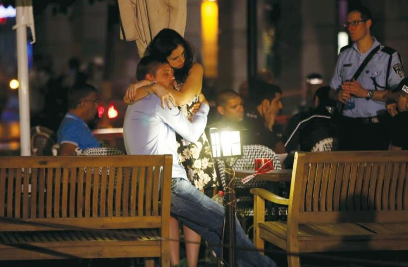 A man and woman comfort each other following the terrorist attack in Tel Aviv last week (photo credit: REUTERS)