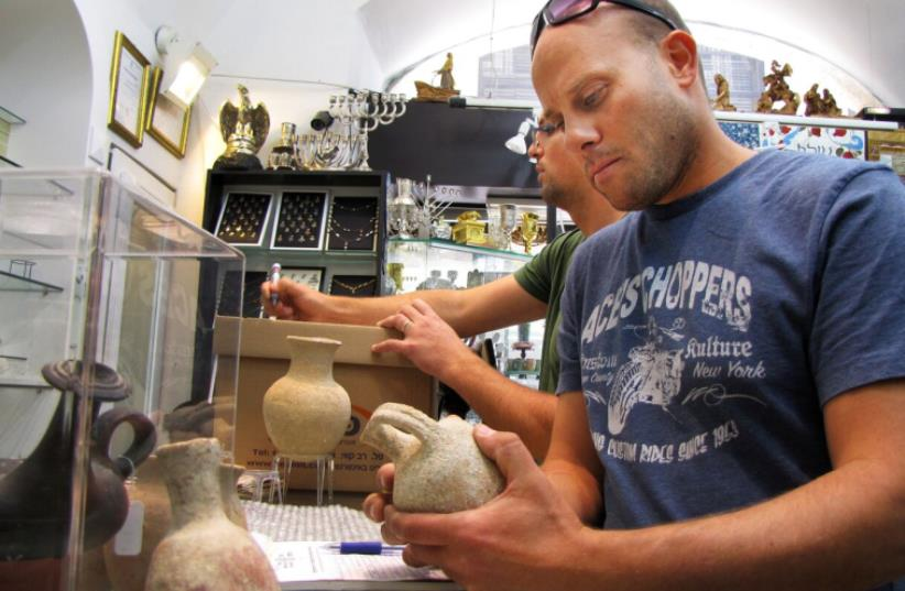 Inspectors from the IAA's Unit for the Prevention of Antiquities >> Robbery during the Tuesday aid of the Mamilla store.  (photo credit: COURTESY OF IAA)