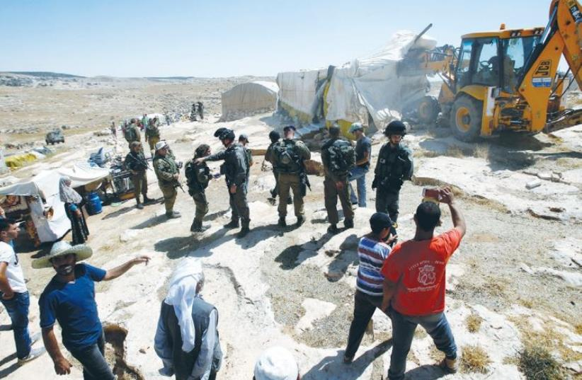 ARMY PERSONNEL demolish illegal sheds near the town of Yatta, south of Hebron yesterday. (photo credit: MUSSA QAWASMA / REUTERS)