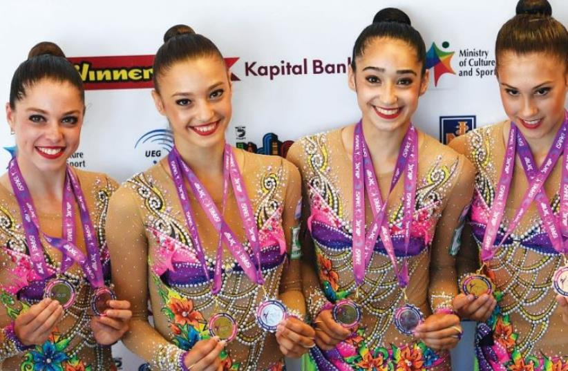 The members of Israel's rhythmic gymnastics national team were understandably delighted on Sunday after claiming the gold medal in the clubs and hoops final at the European Championships in Holon. (photo credit: AMIT SCHUSSEL)