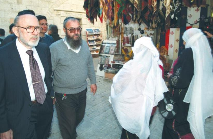 IRVING MOSKOWITZ (left) walks along the Via Dolorosa in Jerusalem's Old City in 1999. Moskowitz, who died Thursday at age 88, helped purchase many buildings in the Old City and in various locations in eastern Jerusalem. (photo credit: REUTERS)