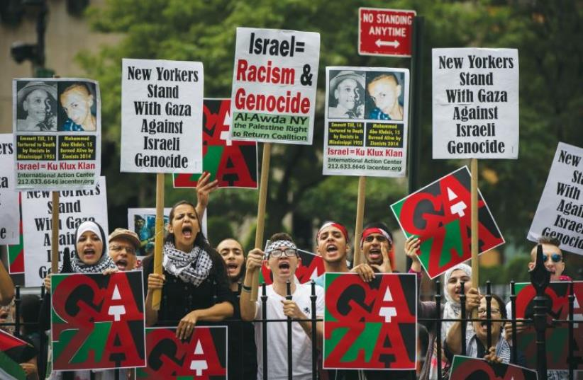 PRO-PALESTINIAN DEMONSTRATORS display signs outside New York's City Hall in July 2014, near where a pro-Israel rally was taking place. (photo credit: LUCAS JACKSON/REUTERS)