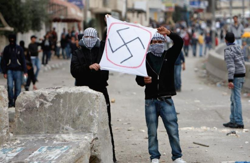 Palestinians hold a sign depicting a swastika during clashes at Qalandiya checkpoint near the West Bank city of Ramallah in 2010. (photo credit: REUTERS)