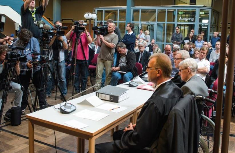 JOURNALISTS TAKE pictures of defendant Reinhold Hanning, a 94-year-old former guard at the Auschwitz death camp, before his verdict in Detmold, Germany. (photo credit: REUTERS)
