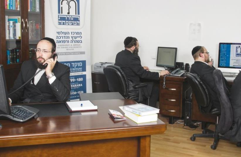 Rabbi Yitzchak Melber (left) and volunteers answer the Tahareinu hotline, fielding questions on Halacha and reproductive health (photo credit: COURTESY TAHAREINU)