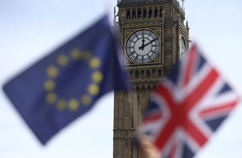 Participants hold a British Union flag and an EU flag during a pro-EU referendum event at Parliament Square in London, Britain June 19, 2016. (photo credit: REUTERS)