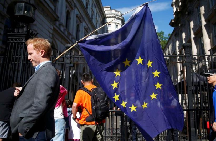 A man carries a EU flag, after Britain voted to leave the European Union (photo credit: REUTERS)