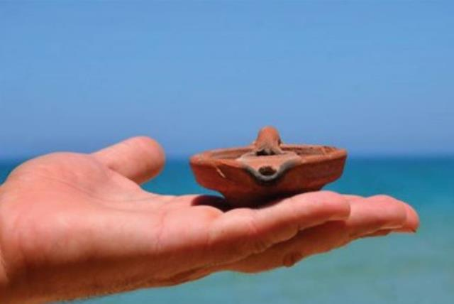 ASHKELON LIFEGUARD Meir Amsik (inset) displays the Crusader-era oil lamp he discovered recently on the beach (photo credit: Courtesy)