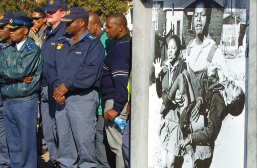 POLICEMEN STAND during the anniversary of the Soweto Uprising, marked every year, in Soweto, 2006. Dozens of black high school students were killed by white security forces on June 16, 1976, during a protest directed at the insistence that students be taught in Afrikaans, seen then as the language o (photo credit: SIPHIWE SIBEKO/REUTERS)