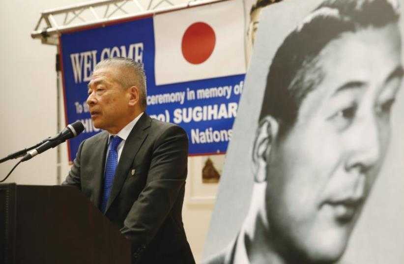NOBUKI SUGIHARA, son of Japanese diplomat, Chiune Sugihara (in black and white picture), who helped save thousands of Lithuanian Jews in World War II, speaks during a street-naming ceremony in honor of his father in Netanya, earlier this month. (photo credit: REUTERS/BAZ RATNER)