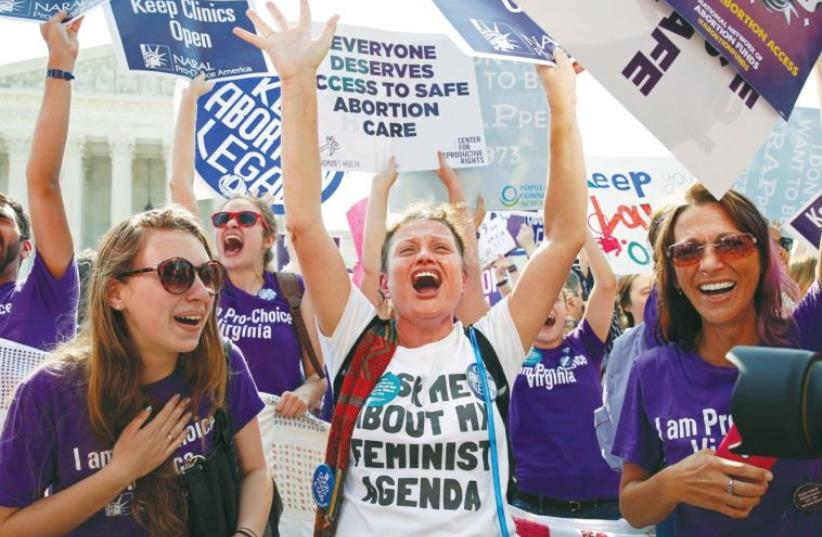 DEMONSTRATORS CELEBRATE at the US Supreme Court in Washington on Monday after the justices struck down a Texas law designed to restrict abortion. (photo credit: KEVIN LAMARQUE/REUTERS)