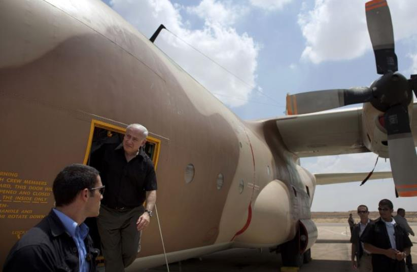 Prime Minister Benjamin Netanyahu during a visit to Hatzerim air base exits a C-130 Hercules aircraft used in the rescue of Israeli hostages at Entebbe in 1976. (photo credit: URIEL SINAI/POOL/REUTERS)