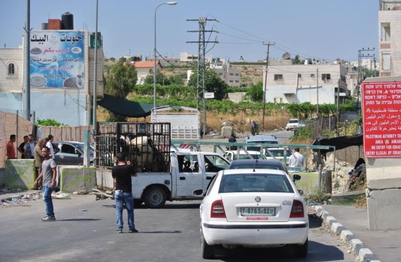 A blocked entrance from route 60 into Sa'ir, a Palestinian village. Men unloading a cow from one truck to another. (photo credit: LAURA KELLY)