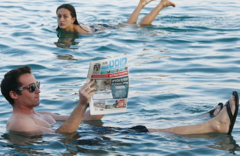 A man reads a newspaper while floating in the Dead Sea (photo credit: MARC ISRAEL SELLEM)