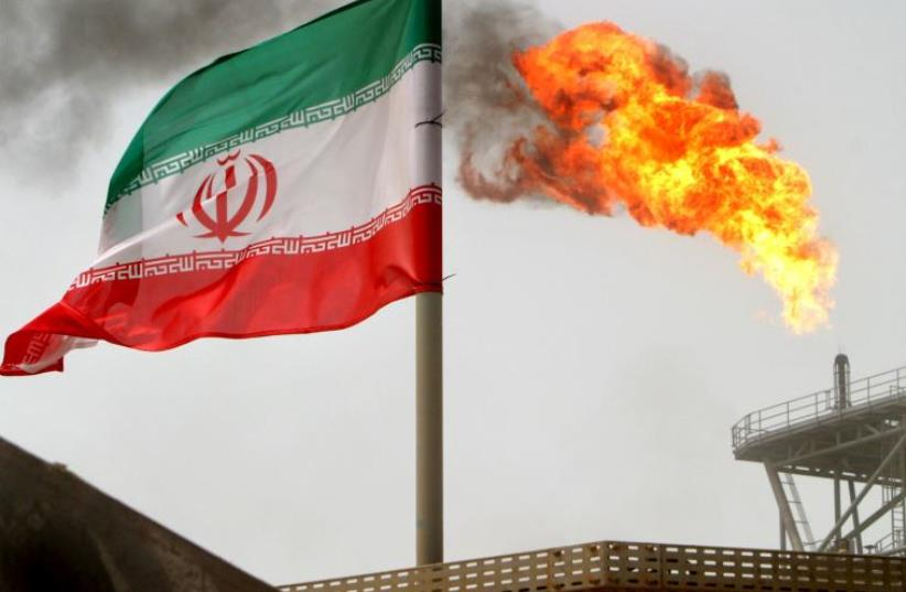 A gas flare on an oil production platform in the Soroush oil fields is seen alongside an Iranian flag in the Gulf  (photo credit: RAHEB HOMAVANDI/REUTERS)